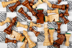 wooden chess pieces scattered on hand drawn chessboard